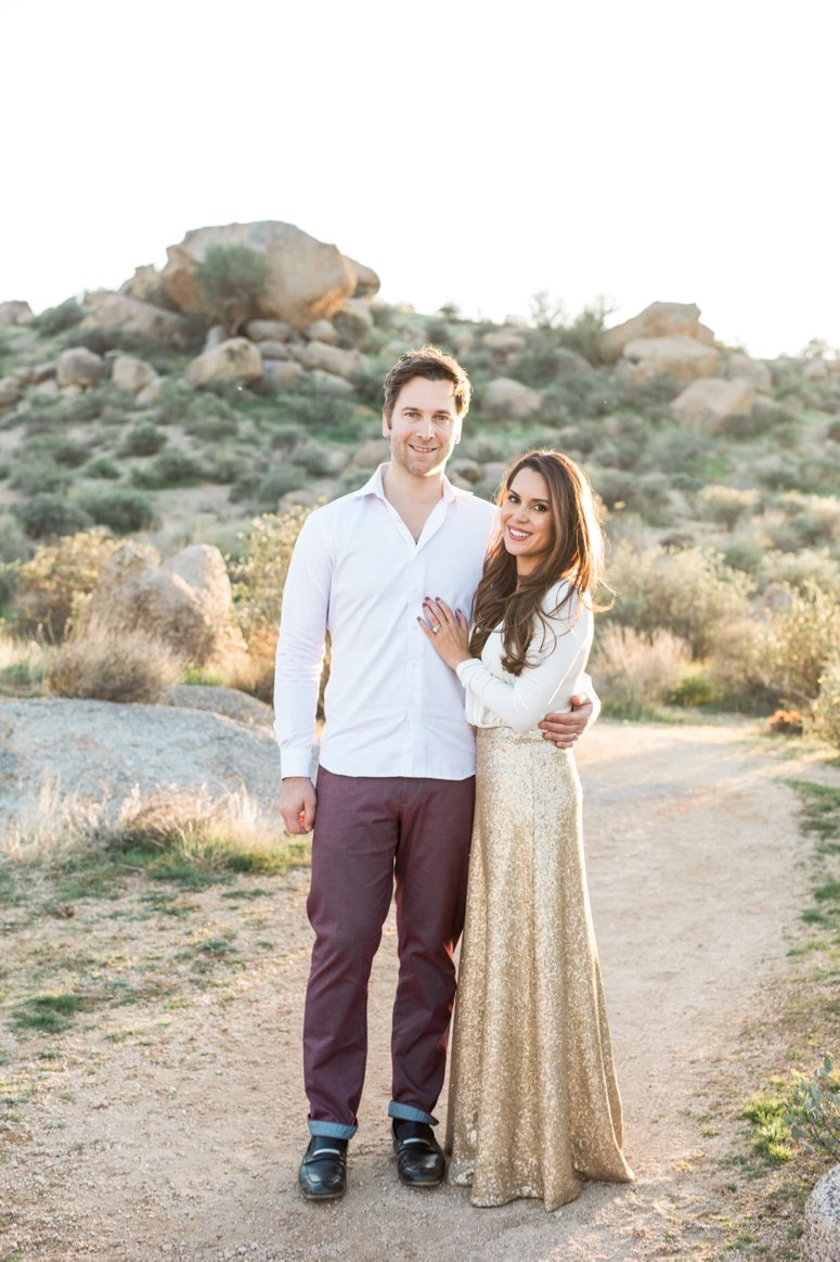 What to wear for family pictures outside | couple standing in desert, woman in gold sequin skirt | lifewithmar.com