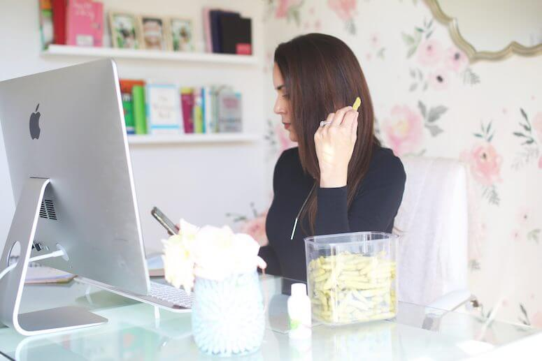brunette woman in feminine office snacking on snap pea crisps   how to stay energized throughout the day as a busy mom