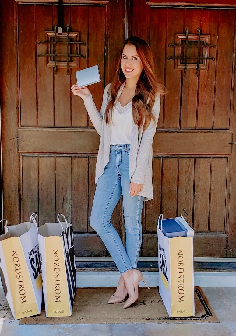 brunette woman with nordstrom anniversary sale shopping tips and bags
