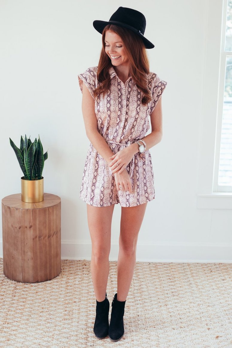 print romper with black ankle boots and black hat