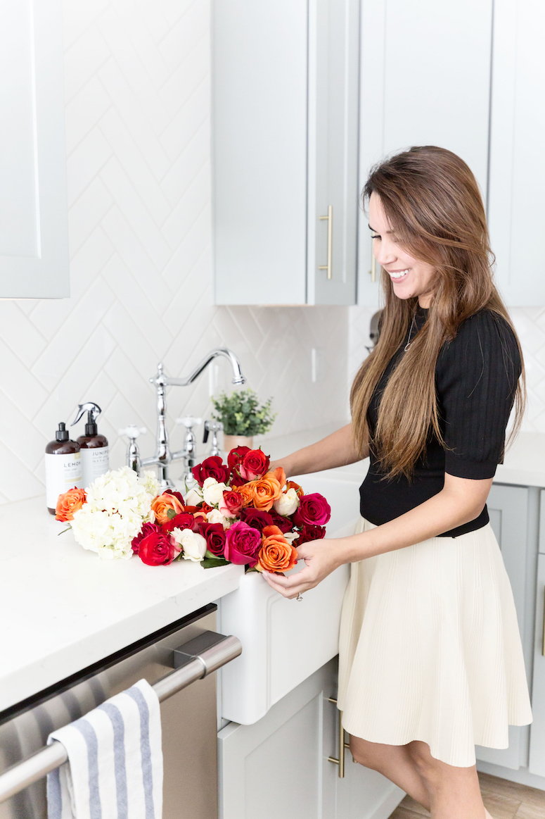 brunette woman at kitchen sink with flowers
