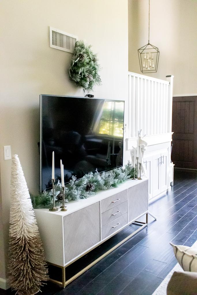 wreath above tv stand living room christmas decor